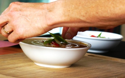 Placing spring onion, roast capsicum and savoury roast seeds carefully on the organic Kumera Carrot Soup