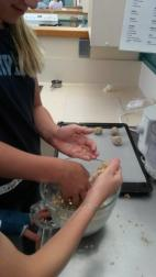 Students forming nutballs for baking in the oven to go with pasta and sauce.