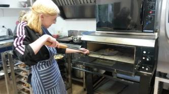Taysha baking a potato-base pizza in the stone oven. Location: Wholegrain Organics, Kimbolton
