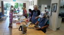 Students topping potato and wheat pizza bases ready to bake in the stone oven. Location: Wholegrain Organics, Kimbolton